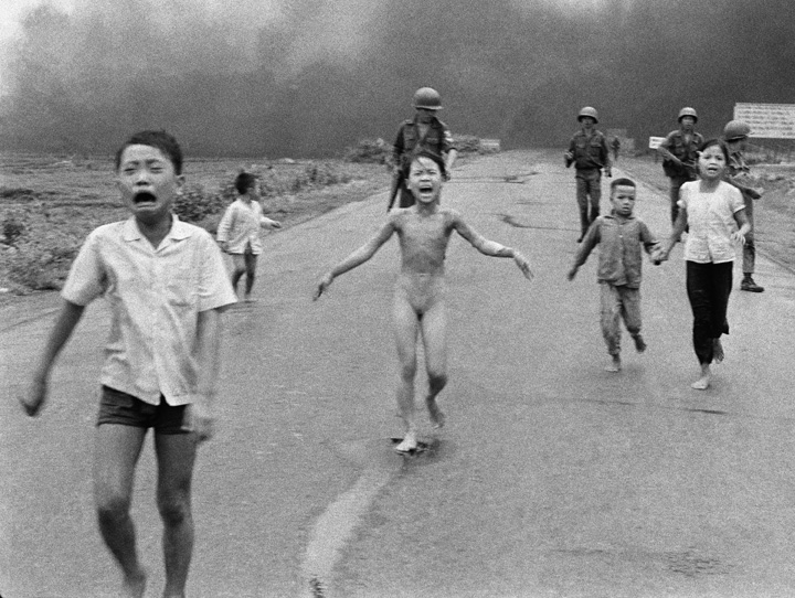 Huynh-Cong-Nick-Ut © 1972 In this June 8, 1972 file photo, crying children, including 9-year-old Kim Phuc, center, run down Route 1 near Trang Bang, Vietnam after an aerial napalm attack on suspected Viet Cong hiding places as South Vietnamese forces from the 25th Division walk behind them. A South Vietnamese plane accidentally dropped its flaming napalm on South Vietnamese troops and civilians. From left, the children are Phan Thanh Tam, younger brother of Kim Phuc, who lost an eye, Phan Thanh Phouc, youngest brother of Kim Phuc, Kim Phuc, and Kim's cousins Ho Van Bon, and Ho Thi Ting. (AP Photo/Nick Ut)