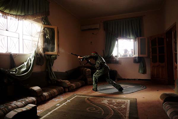 Manu Brabo / AP © Libyan rebel fighter fires his machine gun toward loyalist positions in Sirte, Libya, Oct. 2011